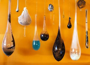 A variety of teardrop shaped glass pieces in a variety of colors and sizes, photographed against an orange background