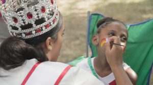 A woman in a crystal and red gem crown paints a rainbow on the face of a young girl sitting in a green chair.